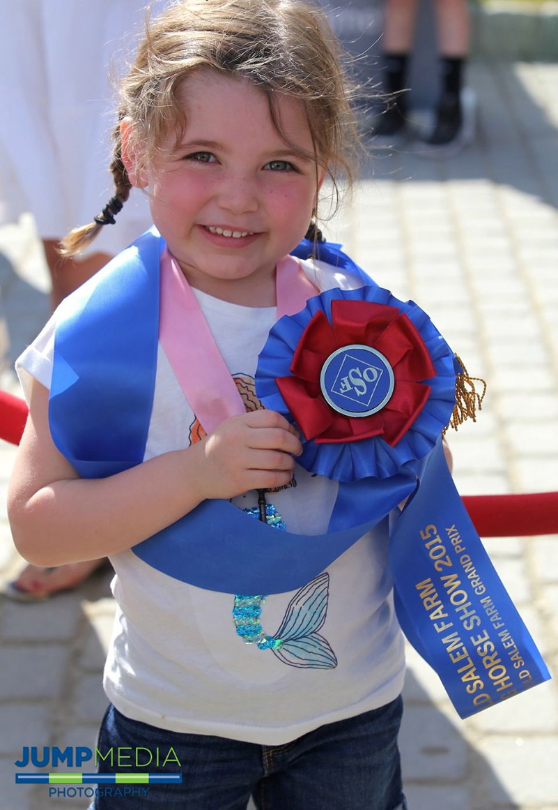 A young show jumping fan shows off a souvenir from The Old Salem Farm Spring Horse Shows; photo © Jump Media