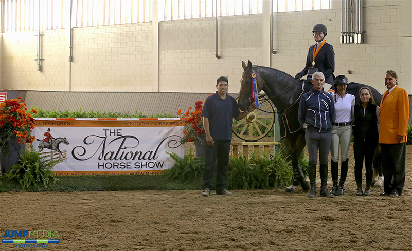 Katherine Bundy, aboard Co Co Pop, with trainers John Brennan, Maggie Gampher, and Kelly Wilson, and groom Roberto Rodriguez are presented as winners of the Region 1 ASPCA/NHSAA Maclay Championship by Mason Phelps, representing the CP National Horse Show; photo © Jump Media