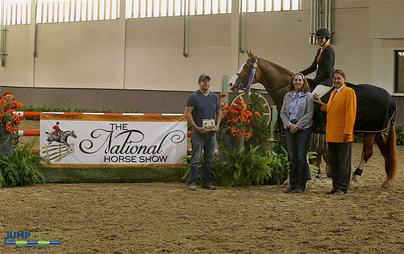 Maya Nayyar, aboard Fox Z, with trainer Stacia Madden and groom Julian Armadillo are presented as winners of the Region 2 ASPCA/NHSAA Maclay Championship by Mason Phelps, representing the CP National Horse Show; photo © Jump Media