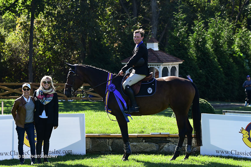 Stephen Moore and Scarlett du Sart Z are presented as winners of the Classic Champions Seven-Year-Old Jumper Final by Cynthia Hampton (left) of Classic Champions and Chelsea Dwinell (right) of Old Salem Farm during the Old Salem Farm Fall Classic at Old Salem Farm in North Salem, NY. Photo by SEL Photography