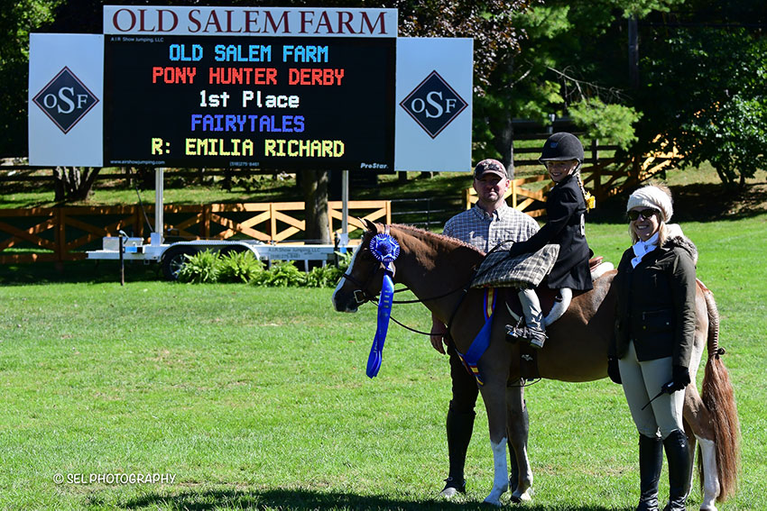 Emilia Richard and Fairytales with trainer Ryan Petronelli (left) are presented as winners of the Pony Hunter Derby by Chelsea Dwinell of Old Salem Farm at the Old Salem Farm Fall Classic in North Salem, NY. Photo by SEL Photography