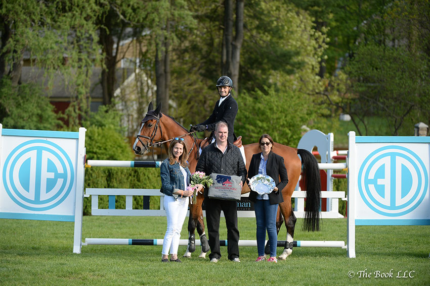 Captain Brian Cournane and Armik are presented as winners of the $35,000 New York Welcome Stake CSI2*, presented by Douglas Elliman Real Estate, by Michael Fitzgibbon (center), Executive Manager of Sales at Douglas Elliman, as well as Camille Branca (left) and Sally Slater (right) of Douglas Elliman Real Estate during the 2018 Old Salem Farm Spring Horse Shows at Old Salem Farm in North Salem, NY. Photo by The Book
